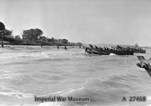 Royal Marines of HMS KENYA dashing ashore on the beach at Cheduba