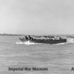 Wooden hulled assault craft with Marines on board nearing the beach at Cheduba